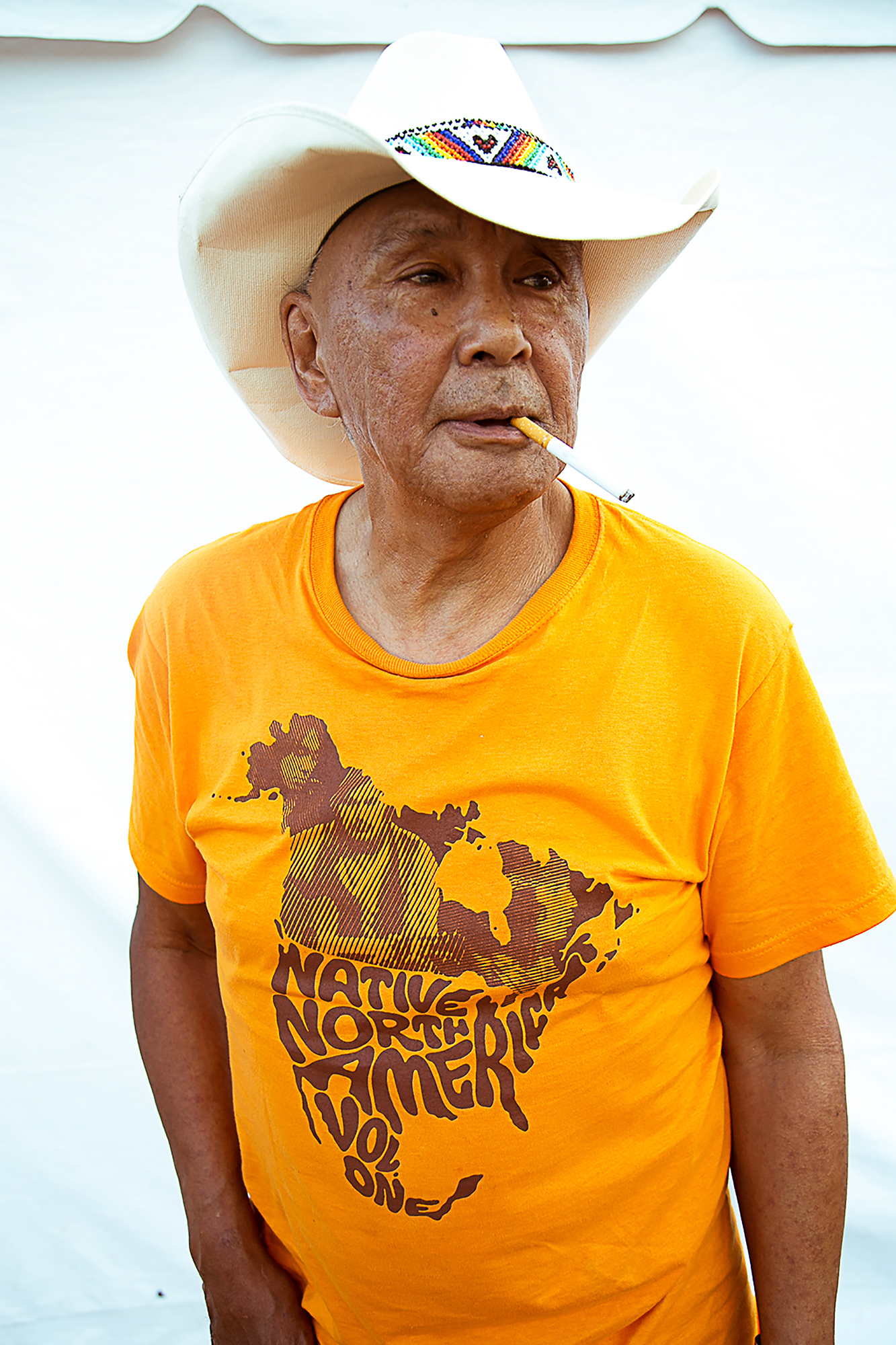 Old Man with a cowboy hat and a bright yellow shirt on smoking a cigarette