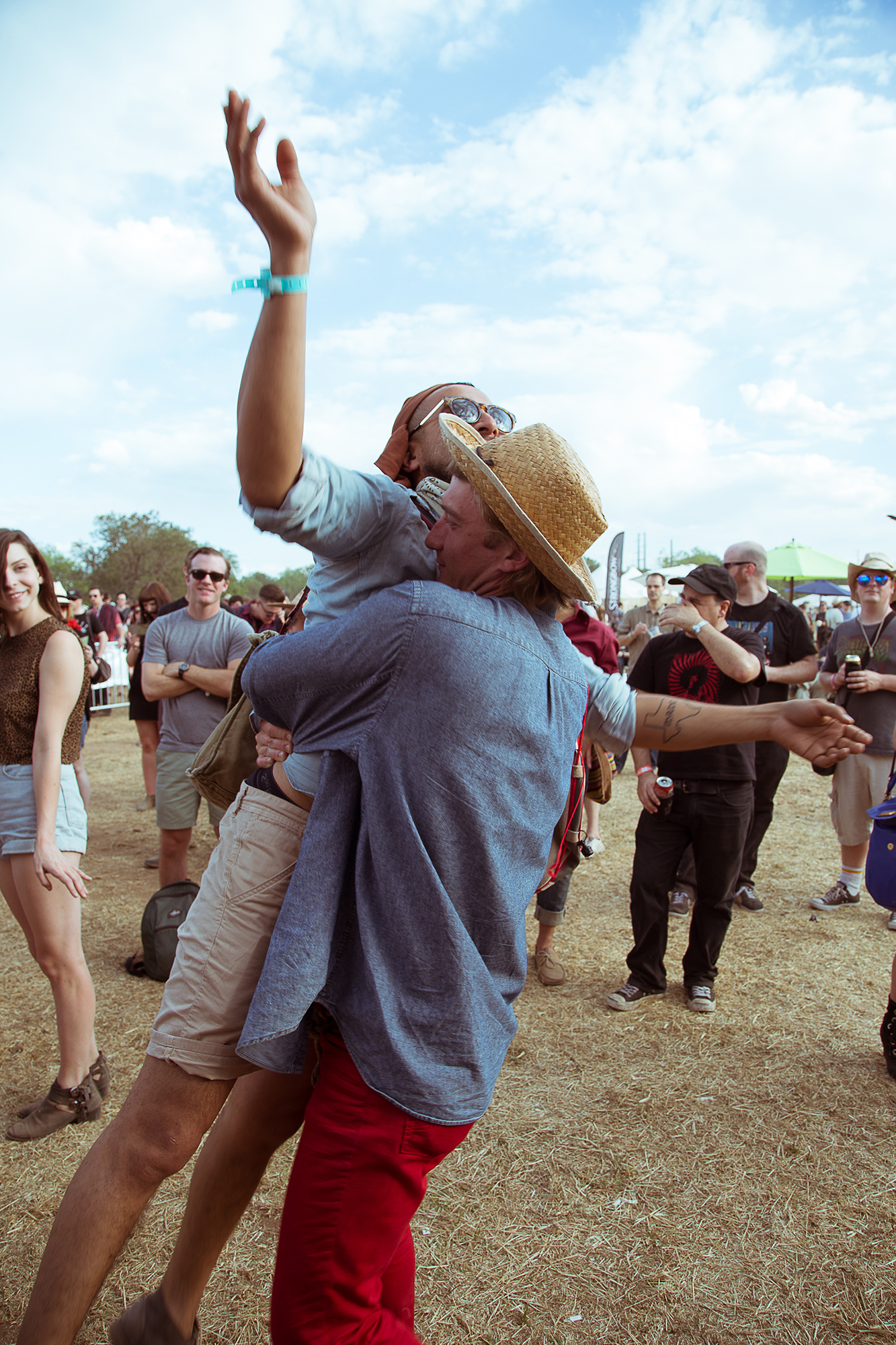 man in straw hat hugs and lifts other man