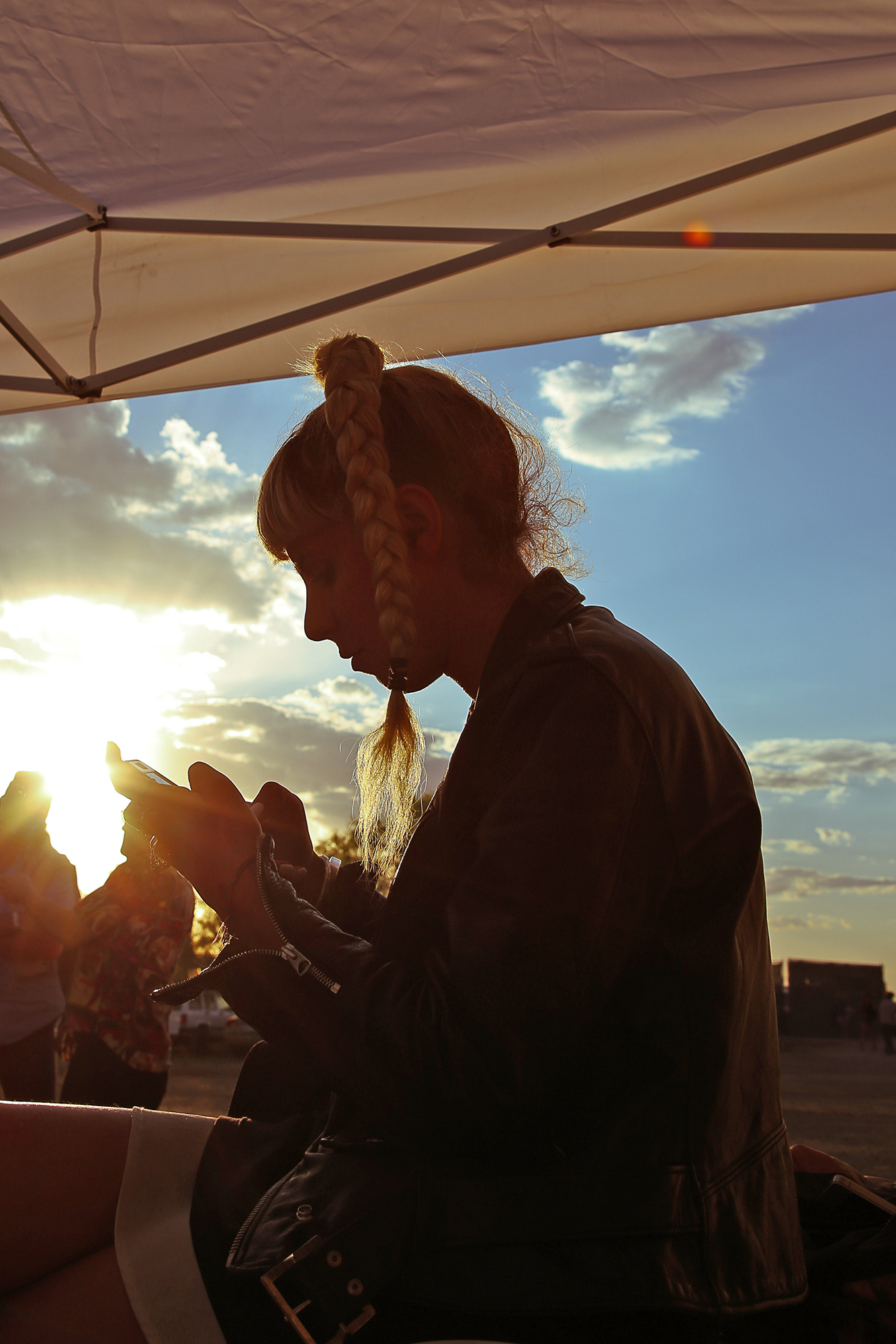 Woman on her phone with the sunset in the background
