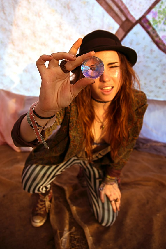 hippie girl looking through a crystal ball in a tent
