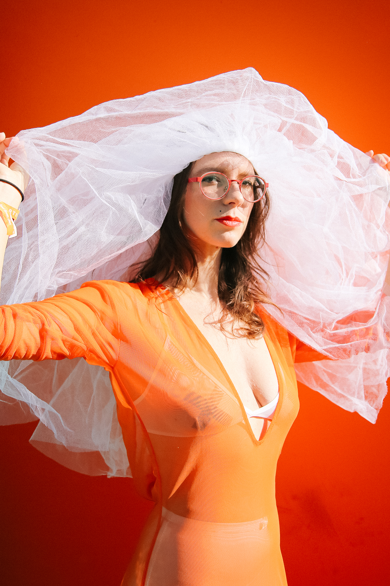 Bright Orange Dress on brunette woman with a white veil