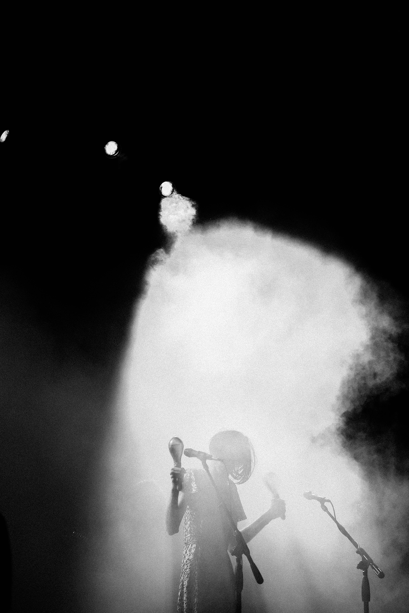 Black and white photograph of lead singer with light shining through the smoke