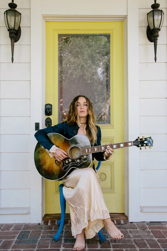 Zella Day playing acoustic guitar