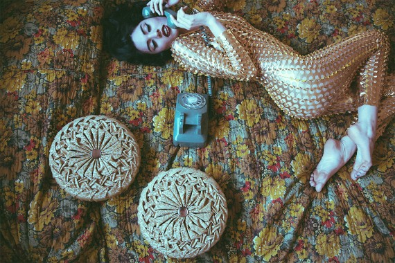 Vintage phone and Gold Jumpsuit skintight lying on 70s' bed bedspread