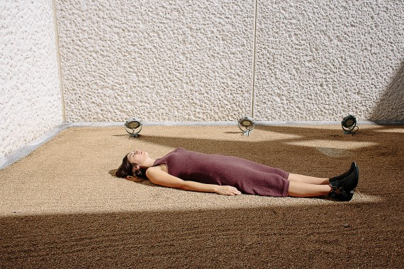 Woman fashion model laying in the sun on a rooftop in a corner in a brown dress lying on the ground