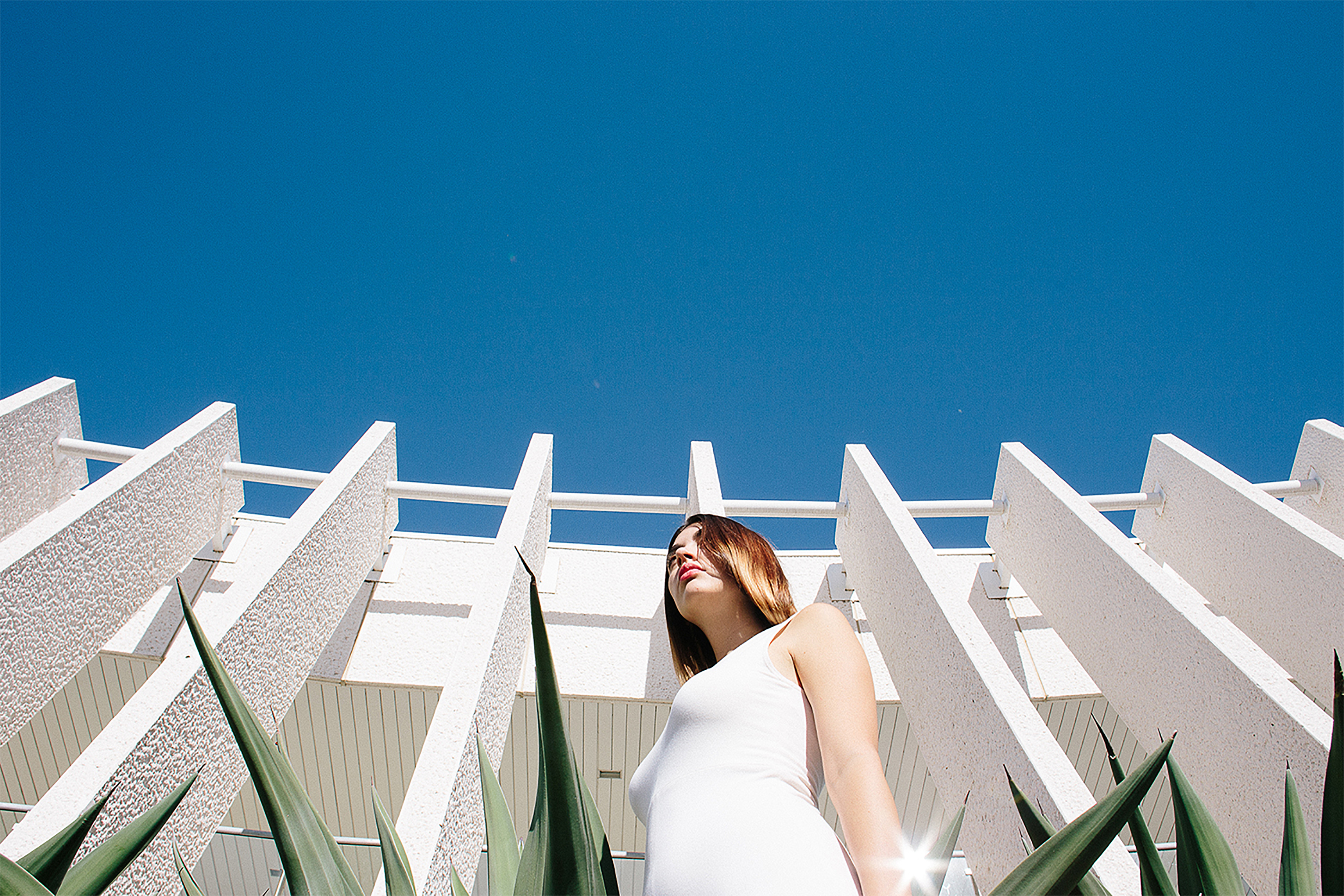 White building and blue skies woman in white dress green plants architecture photography fashion