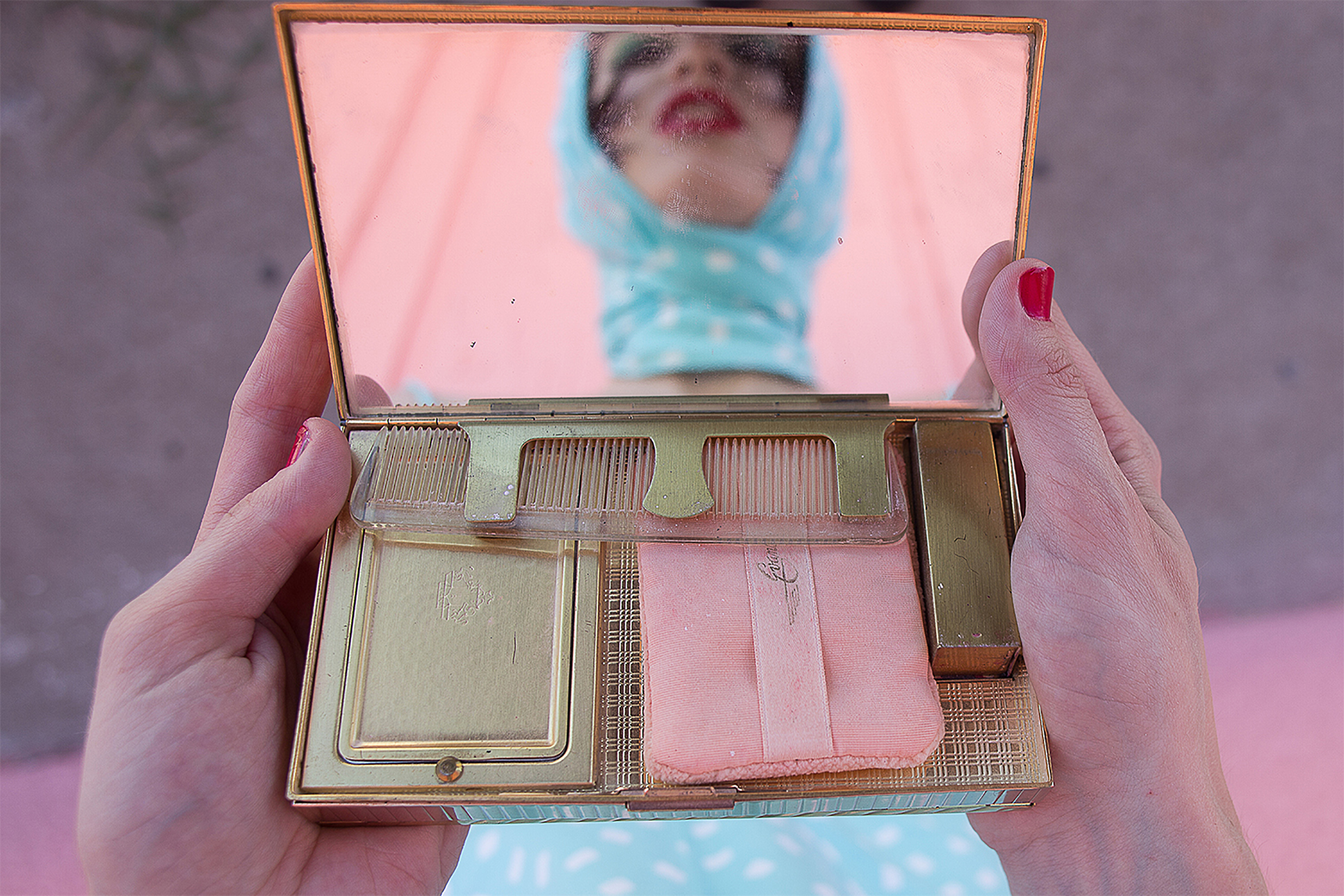 Woman's reflection in a vintage makeup mirror