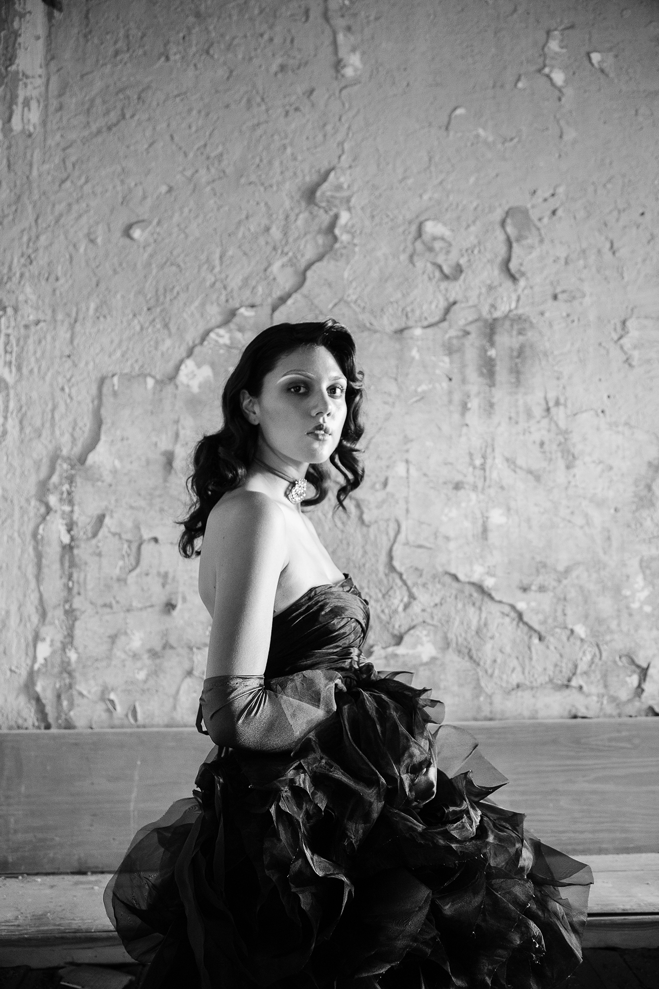 Black and white Photo of woman in a big poofy dress fashion gothic dark photography model body facing way from camera head turned