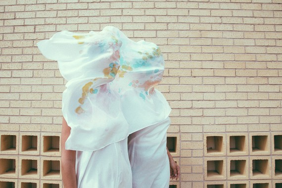 White Dresses and veils covering girls faces in front of a brick wall