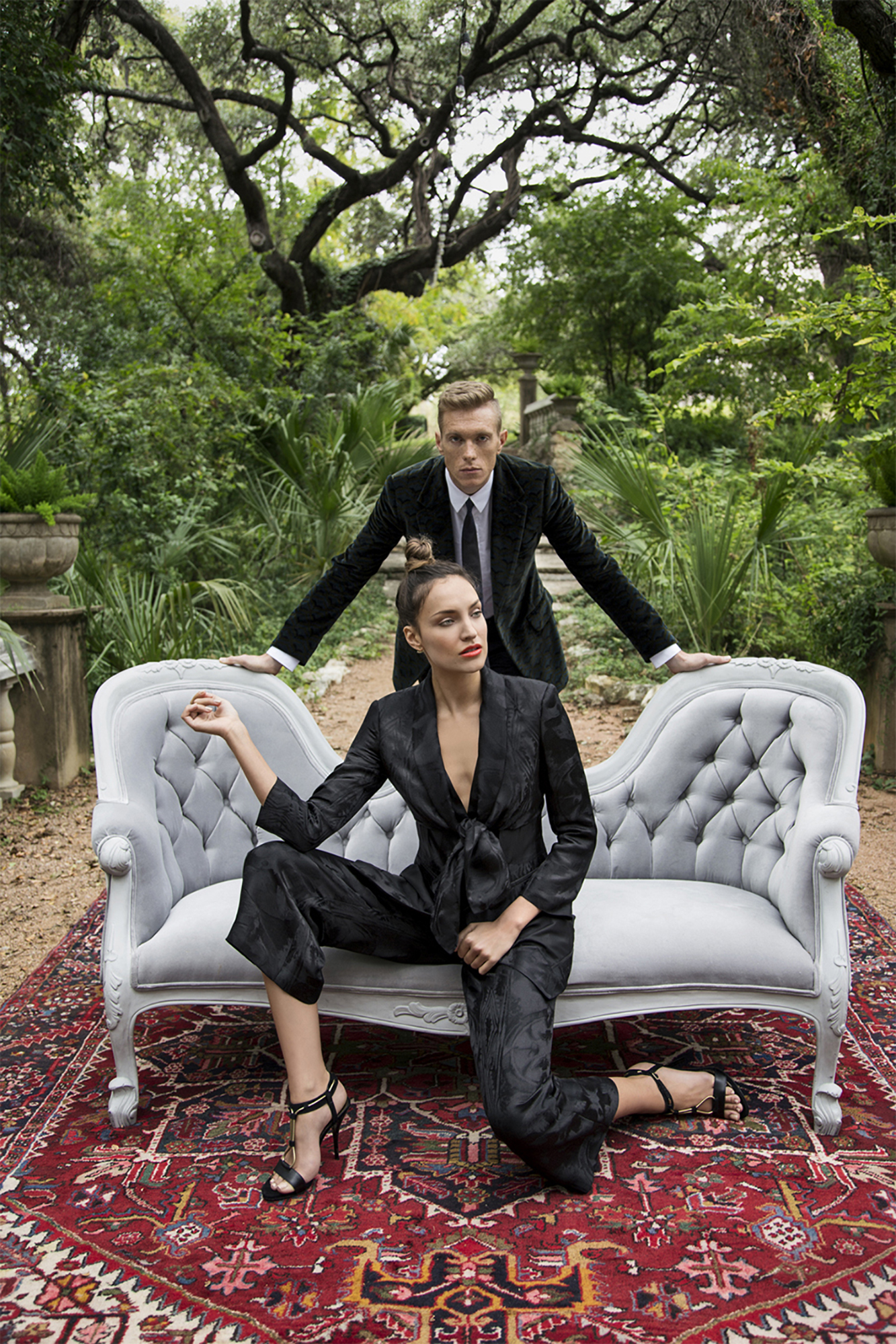 Women's black jumpsuit and men's black suit on sofa in the woods on a rug