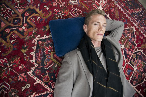 Man laying on a rug in a nice jacket and scarf modeling handsome on rug