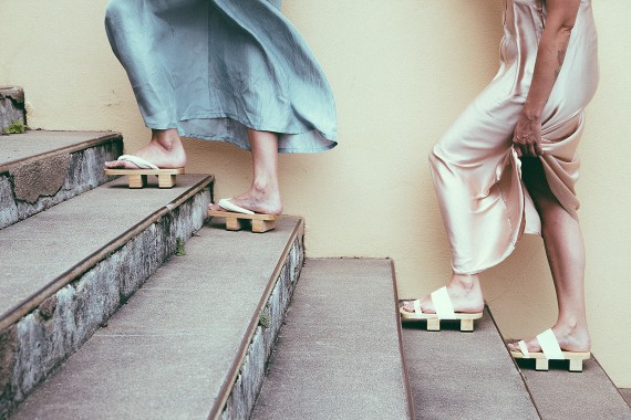 Women walking up the stairs with funky wooden shoes flowy skirts blowing in the wind in front of a yellow wall