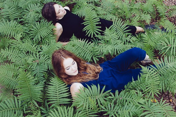 Women laying in the leaves blending into the grass blue dress black