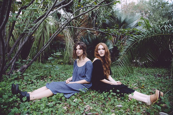 Women's Blue and Black Dresses models sitting in grass backs towards each other
