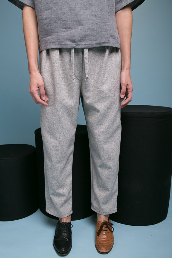 Woman wearing one black shoe and one brown shoe grey sweatpants pants blue wall