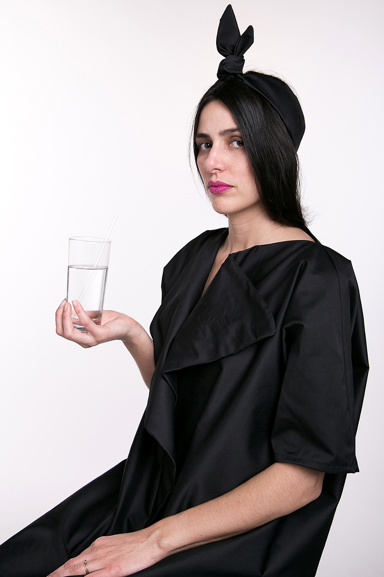Woman in an oversized black dress coat and headband holding a glass of water clear liquid