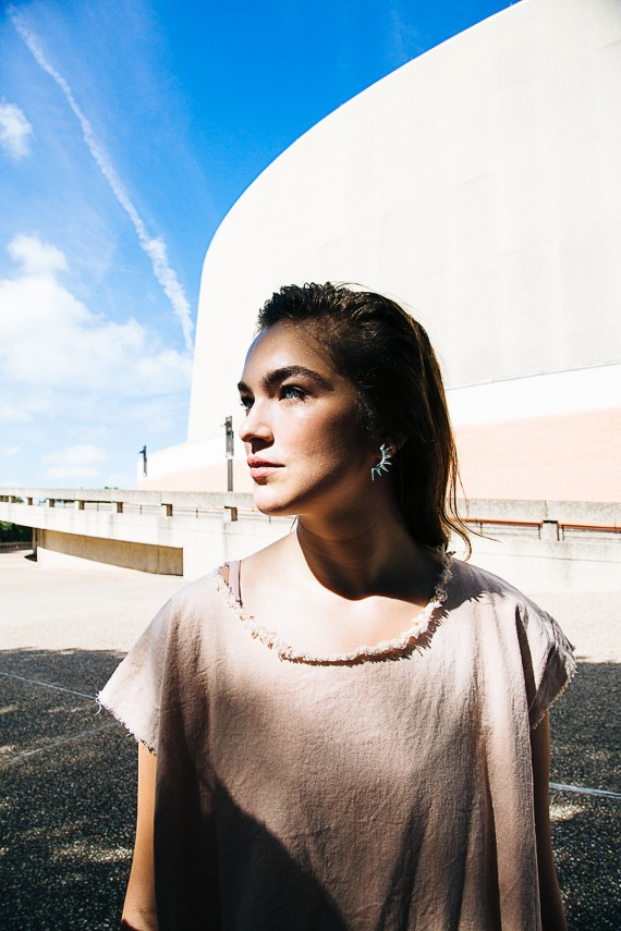 Woman looking off into the distance with blue sky behind her jewelry necklace