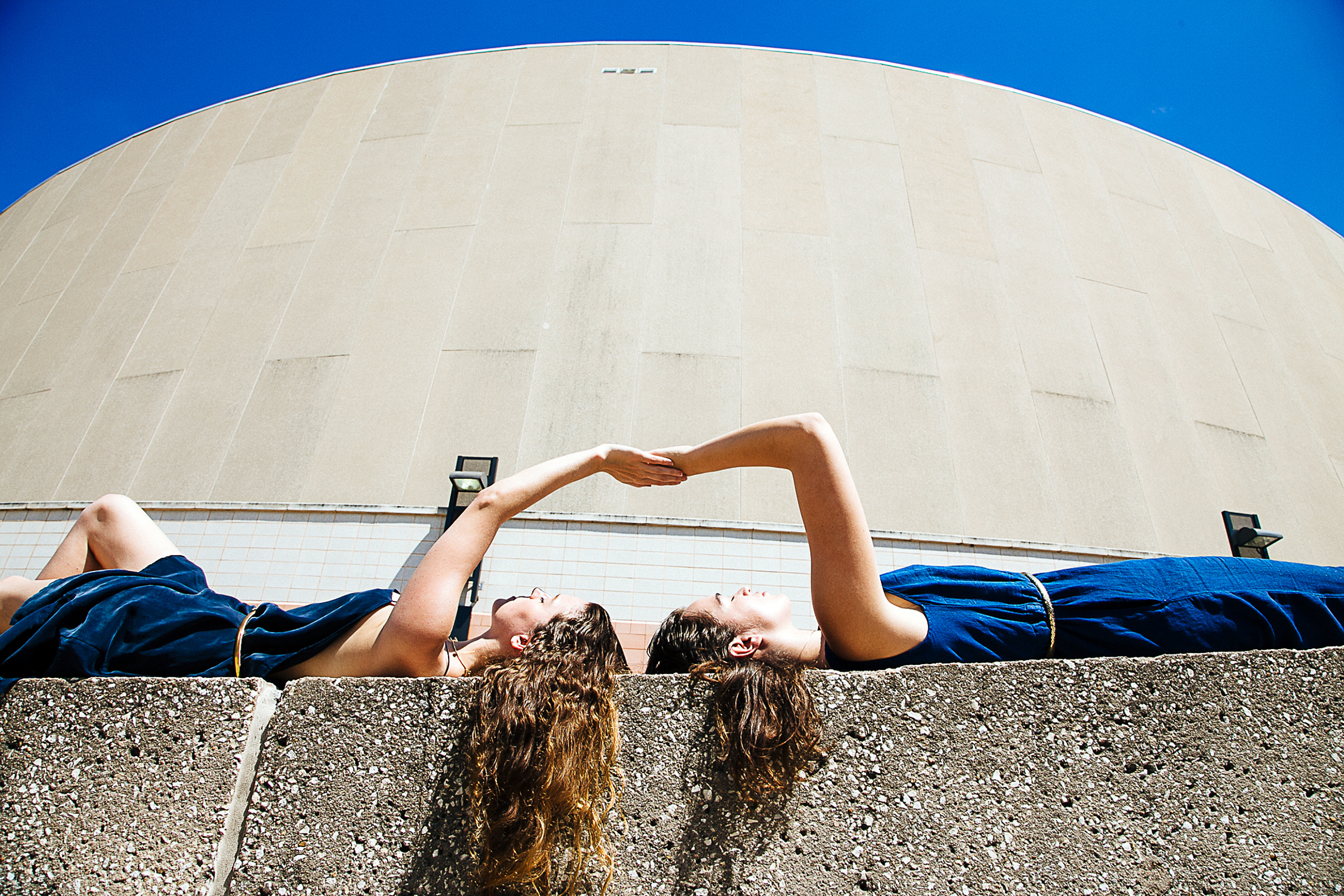 Navy blue dresses and brown curly hair two girls hands touching lying on ledge