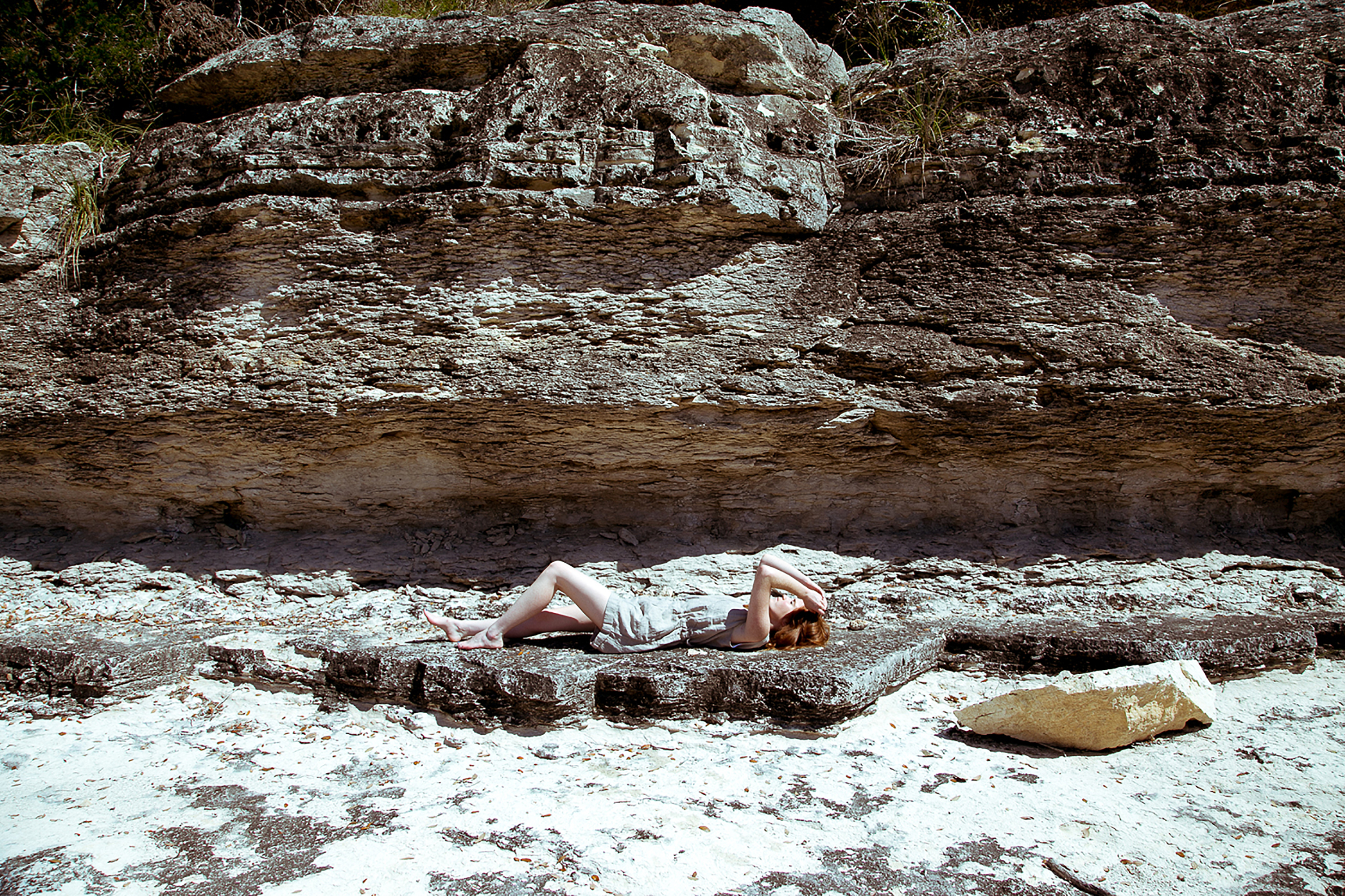 Woman laying on a rocky mountain side on her back covering her eyes