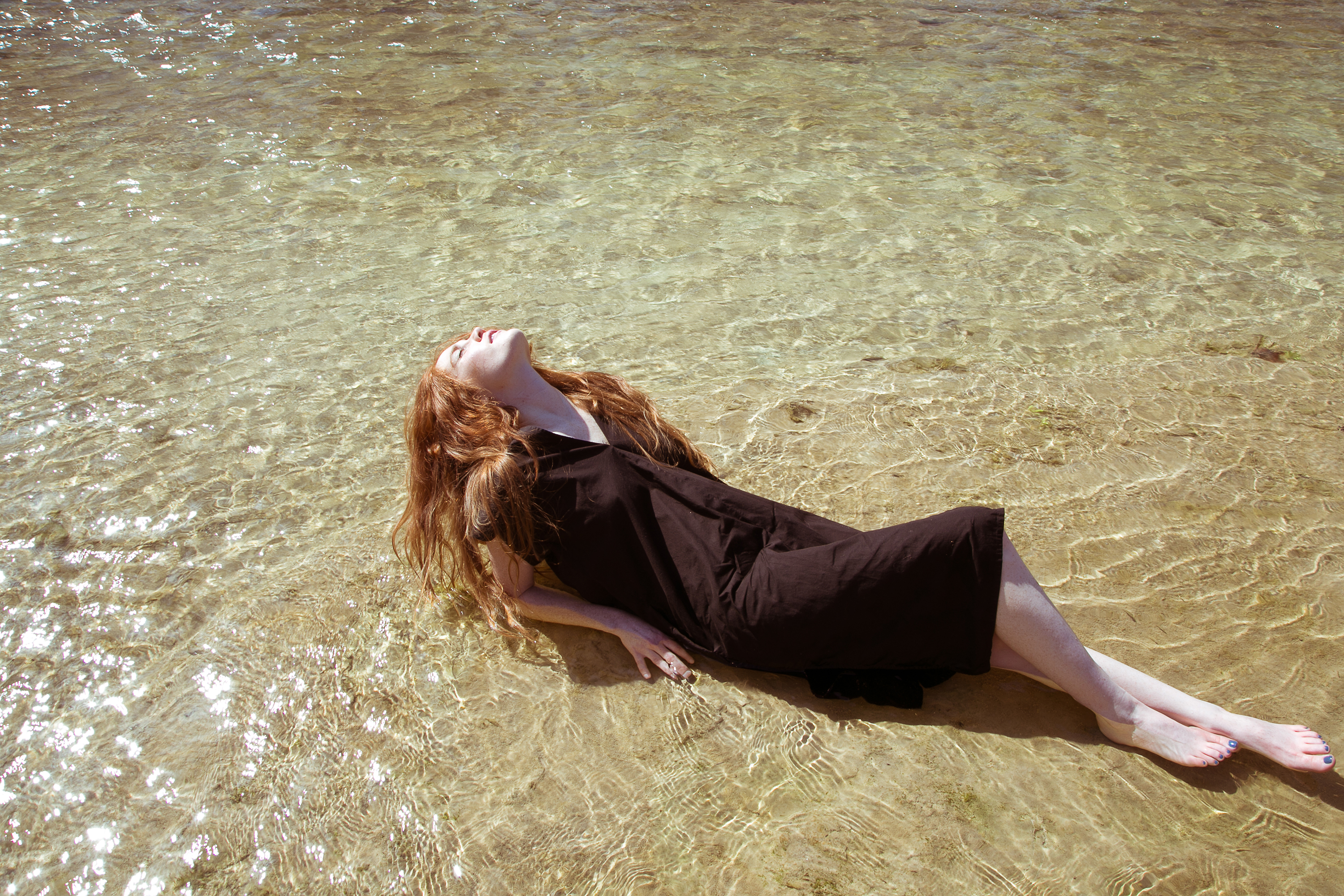 Woman with brown dress on sunbathing in the shallow water
