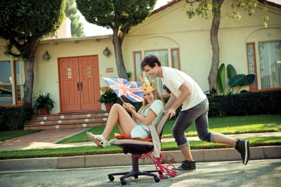 Guy pushing girl down the street in a rolling chair