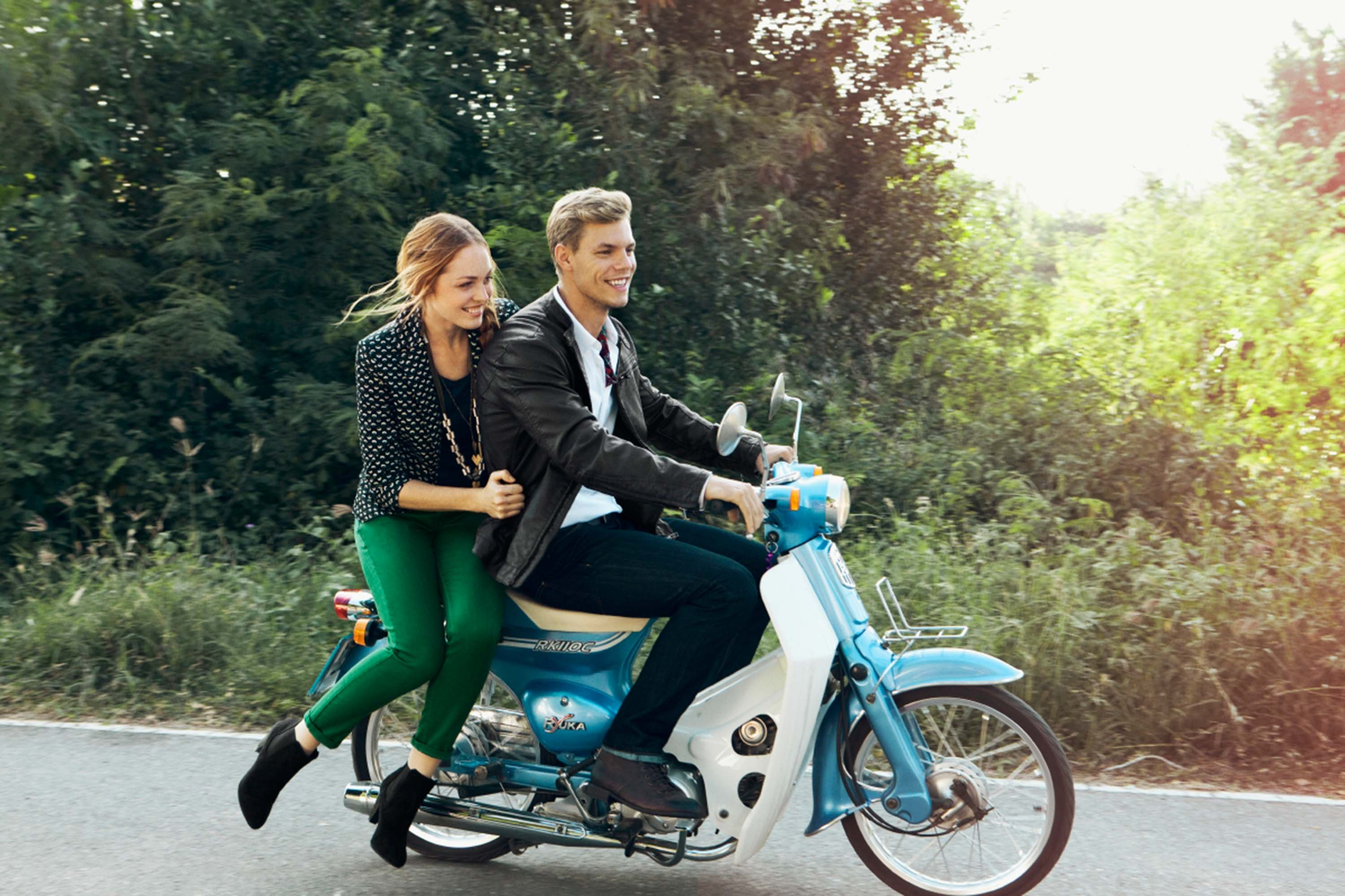 Man and woman riding on a moped