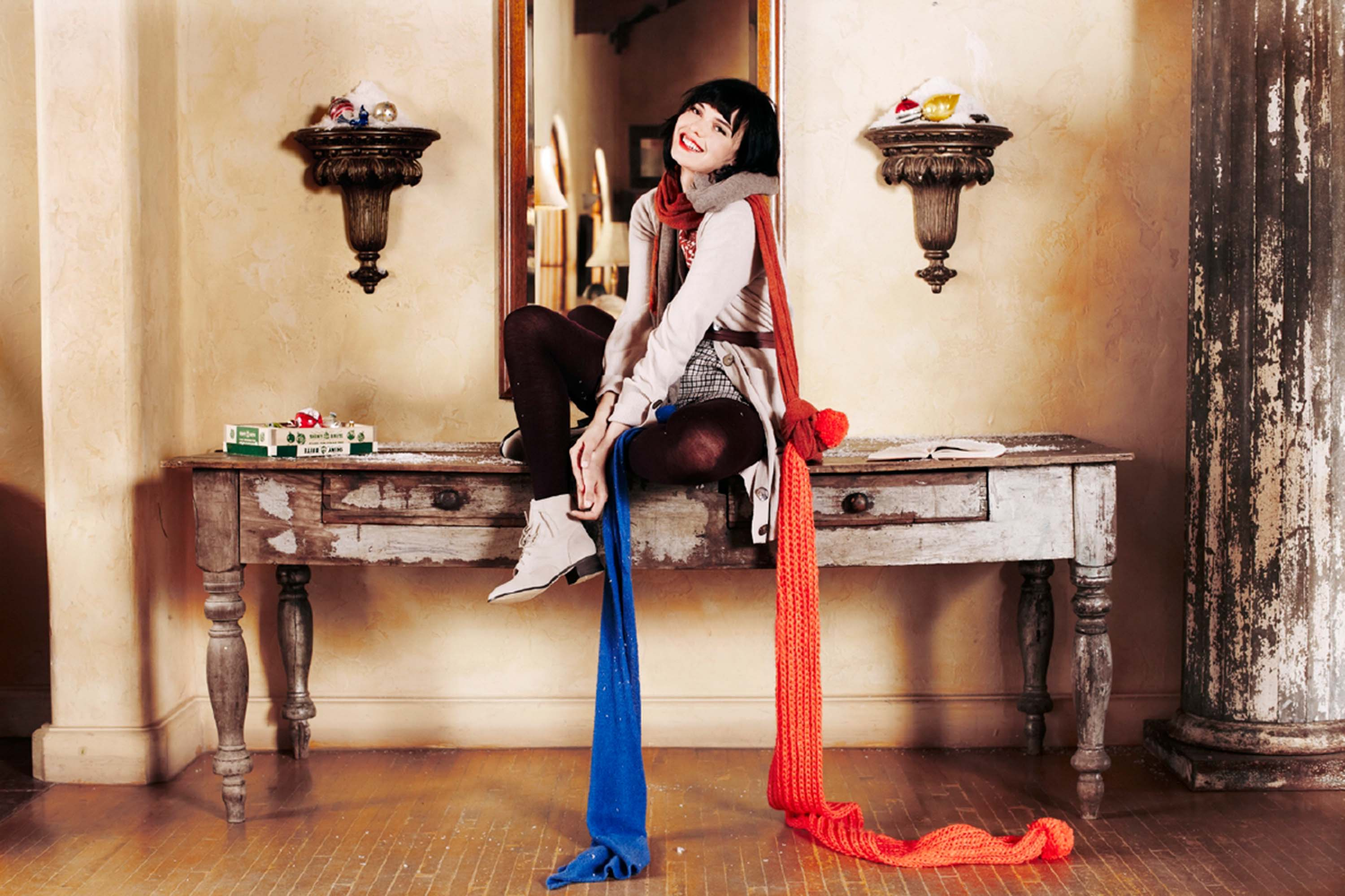 Woman with long blue and red/orange scarves on