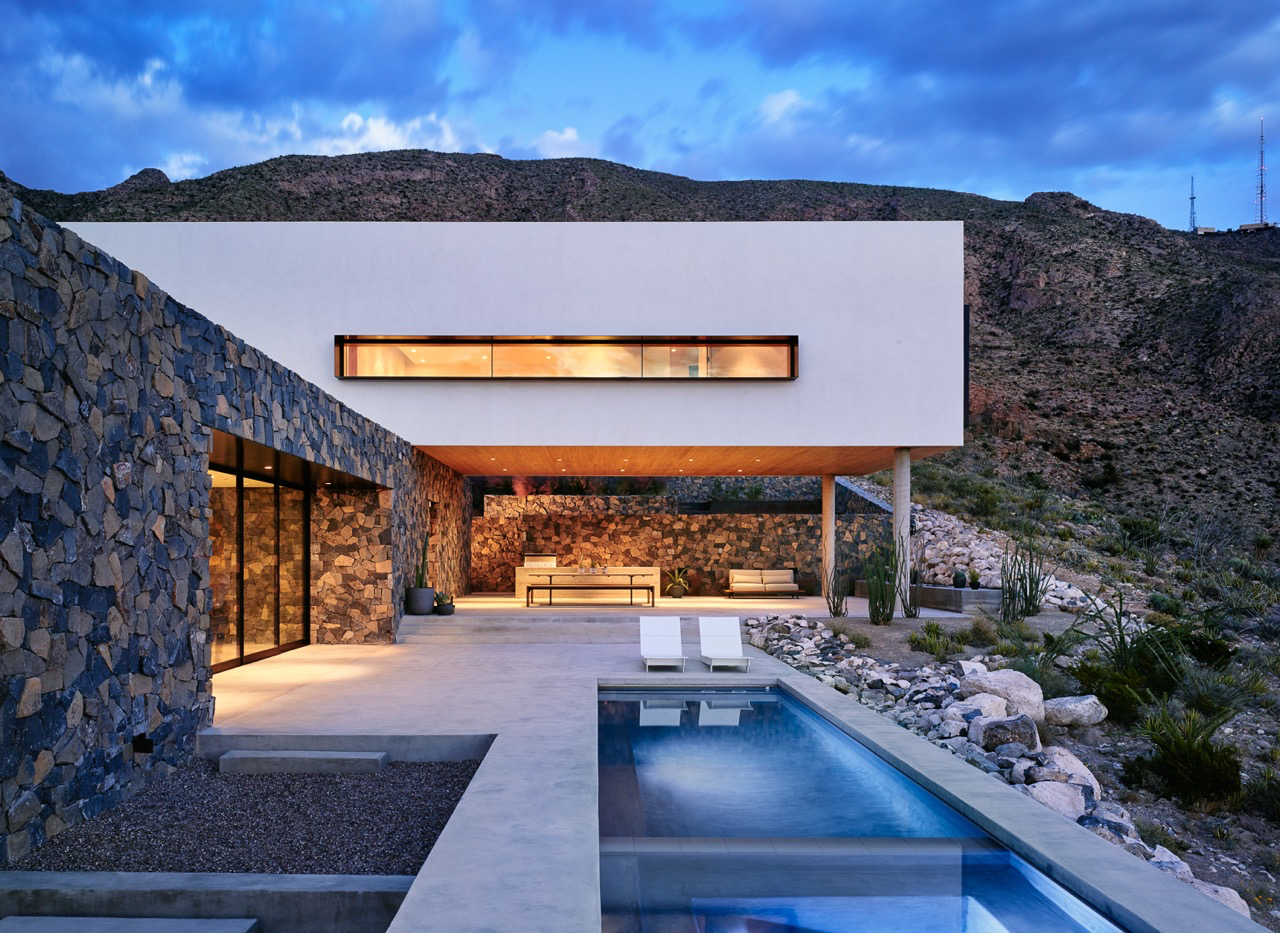 evening view of house with white over hang, pool, and rock sides