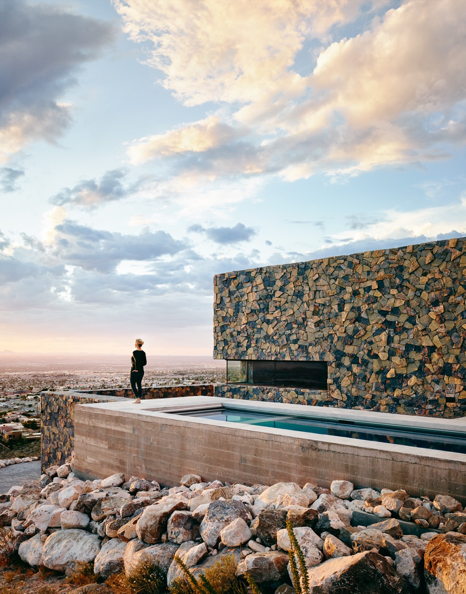 sun setting view of house made of rock with pool
